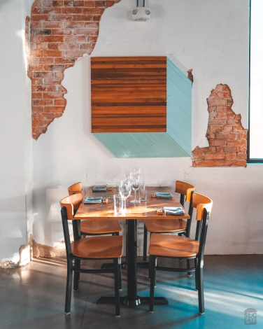 A photo of a restaurant table with glassware and an exposed brick wall