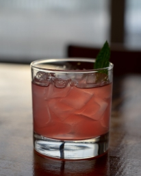 A photo of a pink cocktail with a thai basil leaf garnish