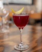 A photo of a red cocktail with a lemon peel garnish