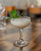 A photo of a cocktail with mint leaf garnish