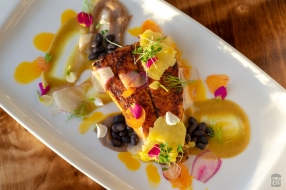 A photo of grilled sea bass with pineapple and beans
