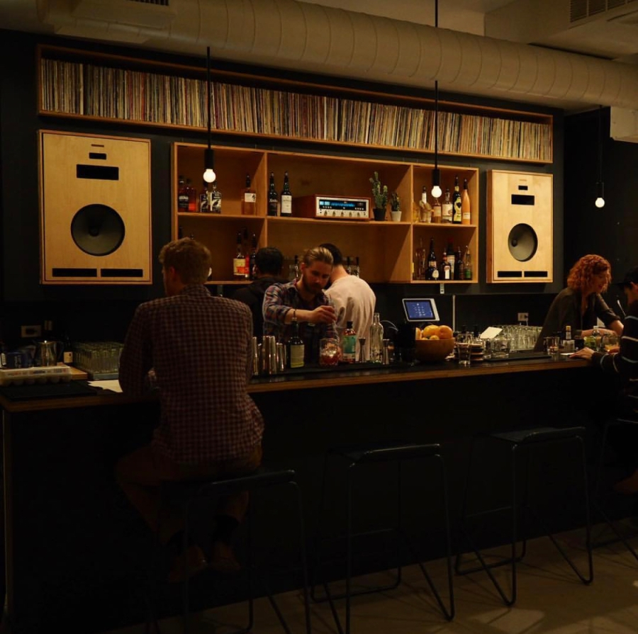 Bartender mixing a cocktail at a bar with vinyl records on the shelf