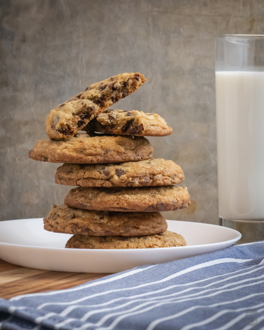 A photo of chocolate chip cookies stacked on top of each other next to a glass of milk